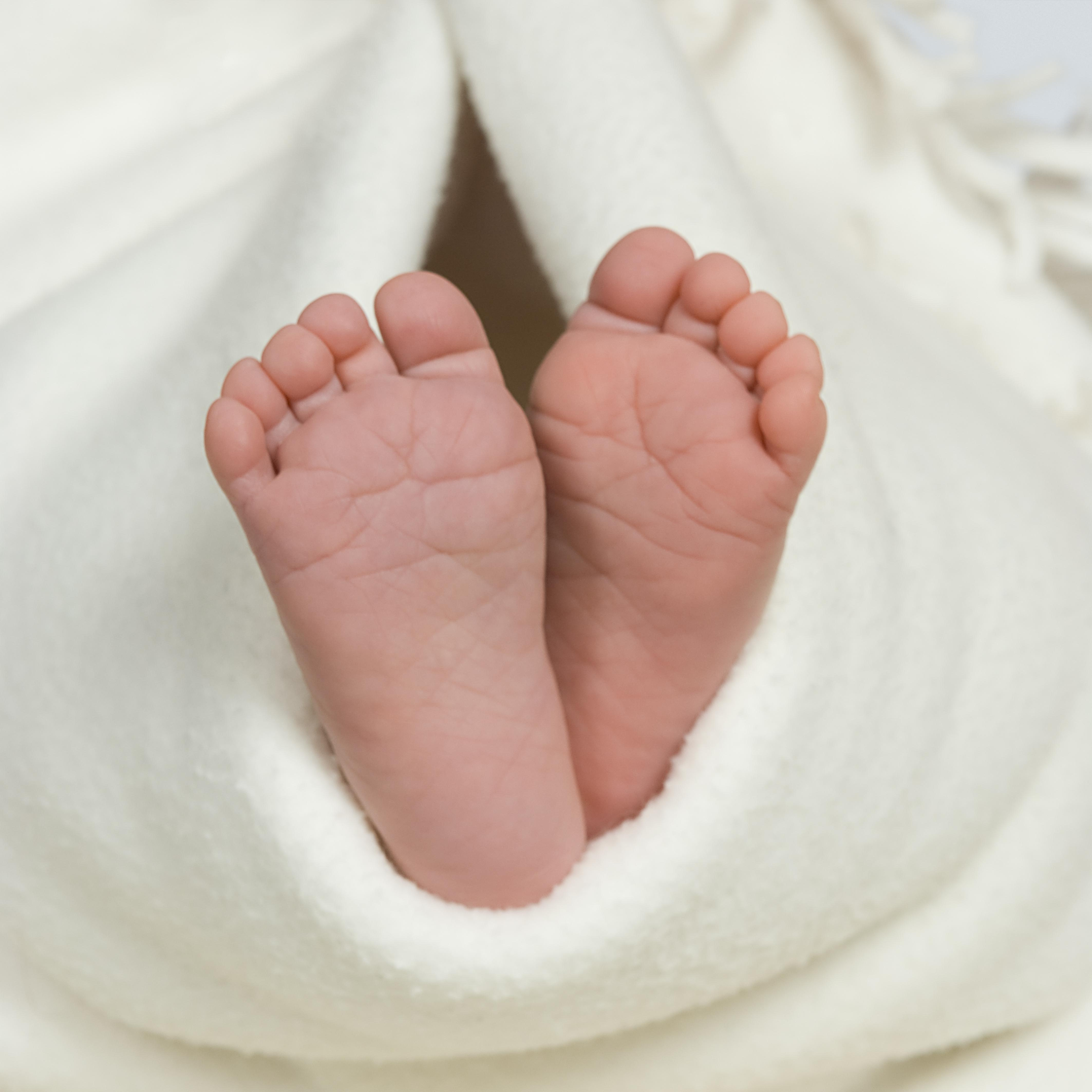Pair of baby's feet poking out from blanket, close-up