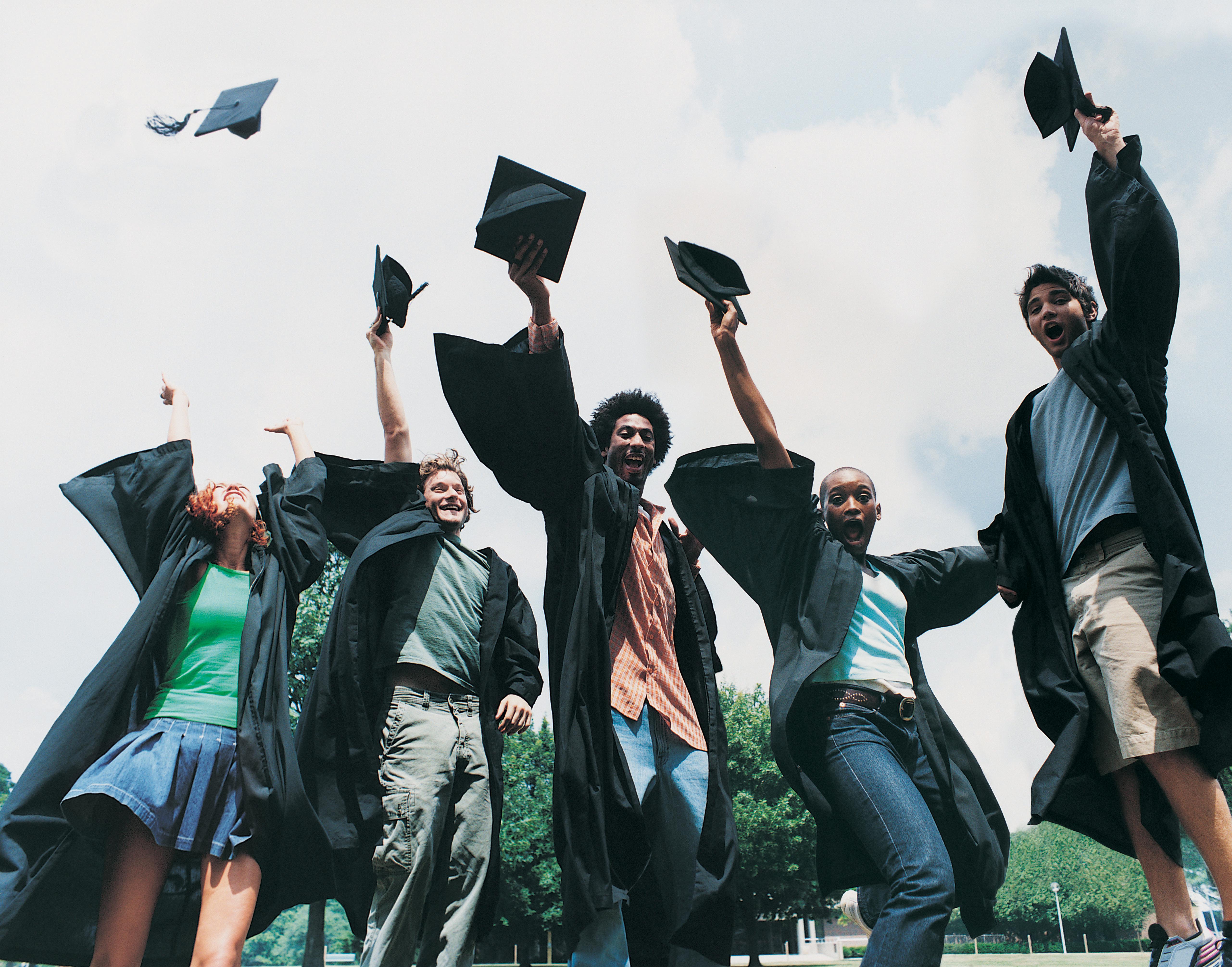Five Students Jumping for Joy at Graduation
