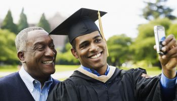 Young man in graduation gown taking self-portrait photograph with father on campus