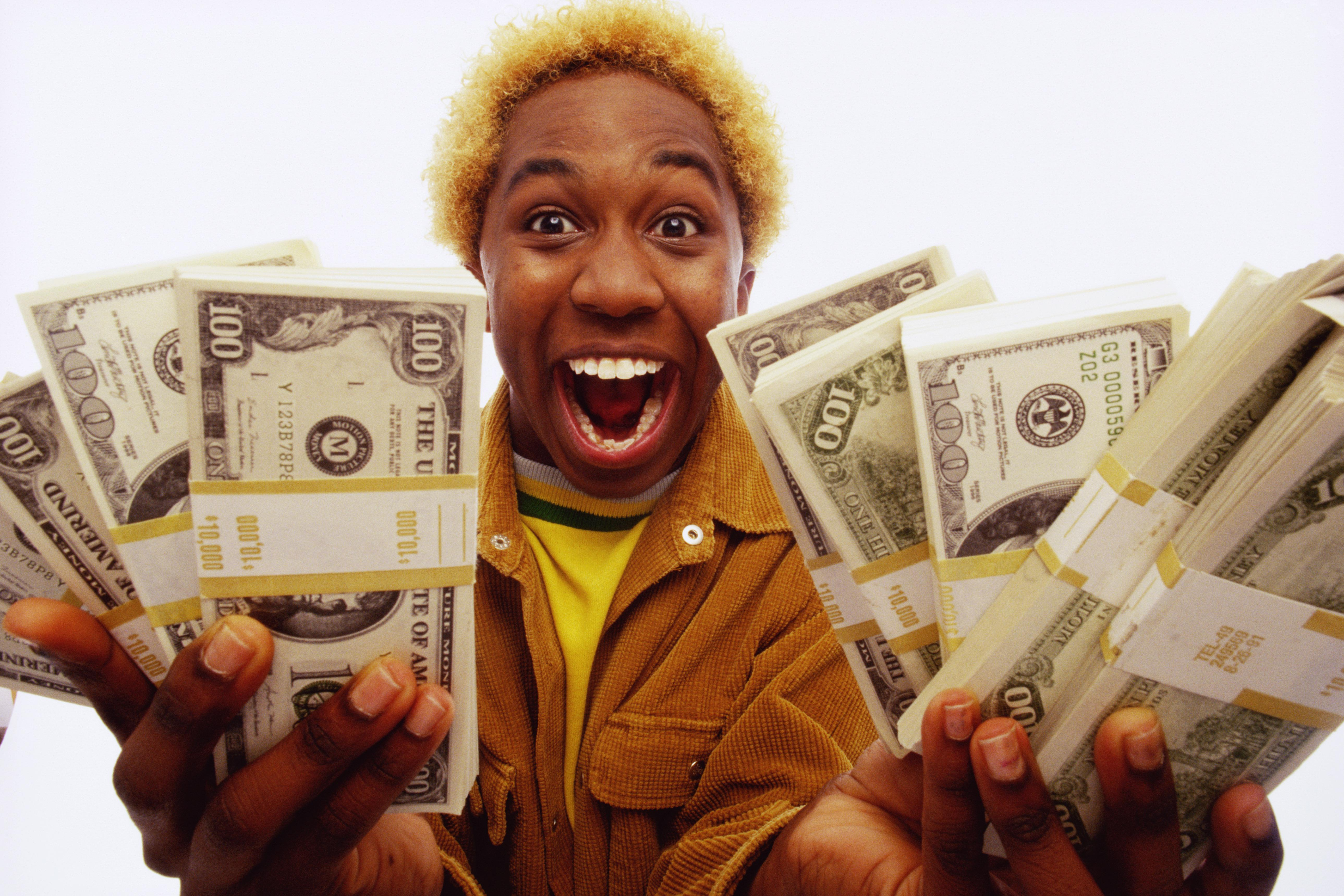 Young man holding bundles of US dollars, smiling, portrait