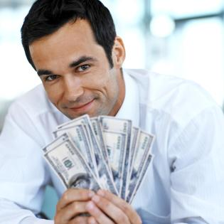 front view portrait of businessman holding a stack of American dollar notes