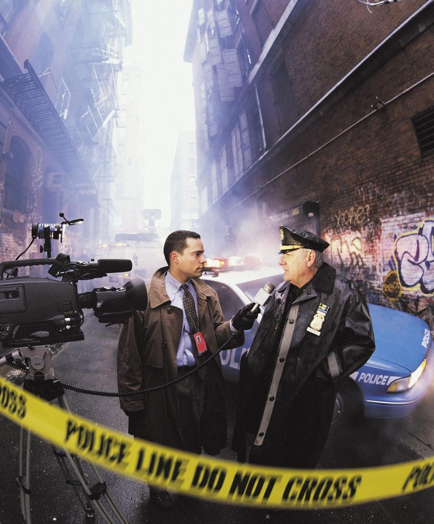News reporter with police officer at crime scene, New York, USA