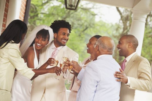 African American newlyweds toasting with family
