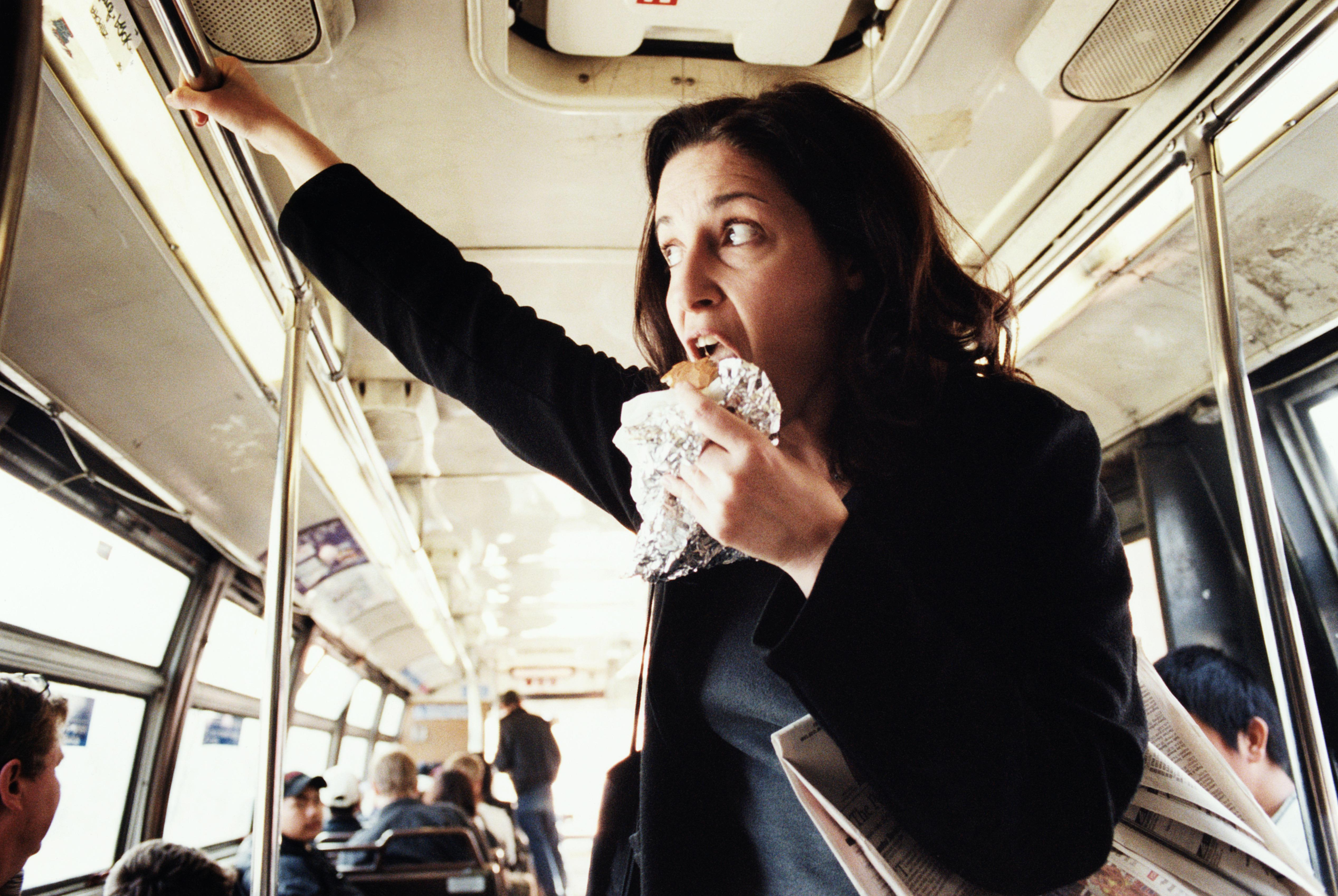 Woman eating hamburger on bus