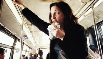 Woman eating hamburger on bus