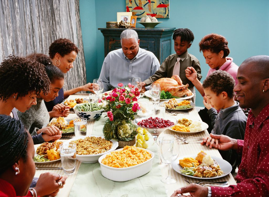 Family Saying Grace at Thanksgiving Dinner