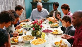 Family Saying Grace at Thanksgiving Dinner