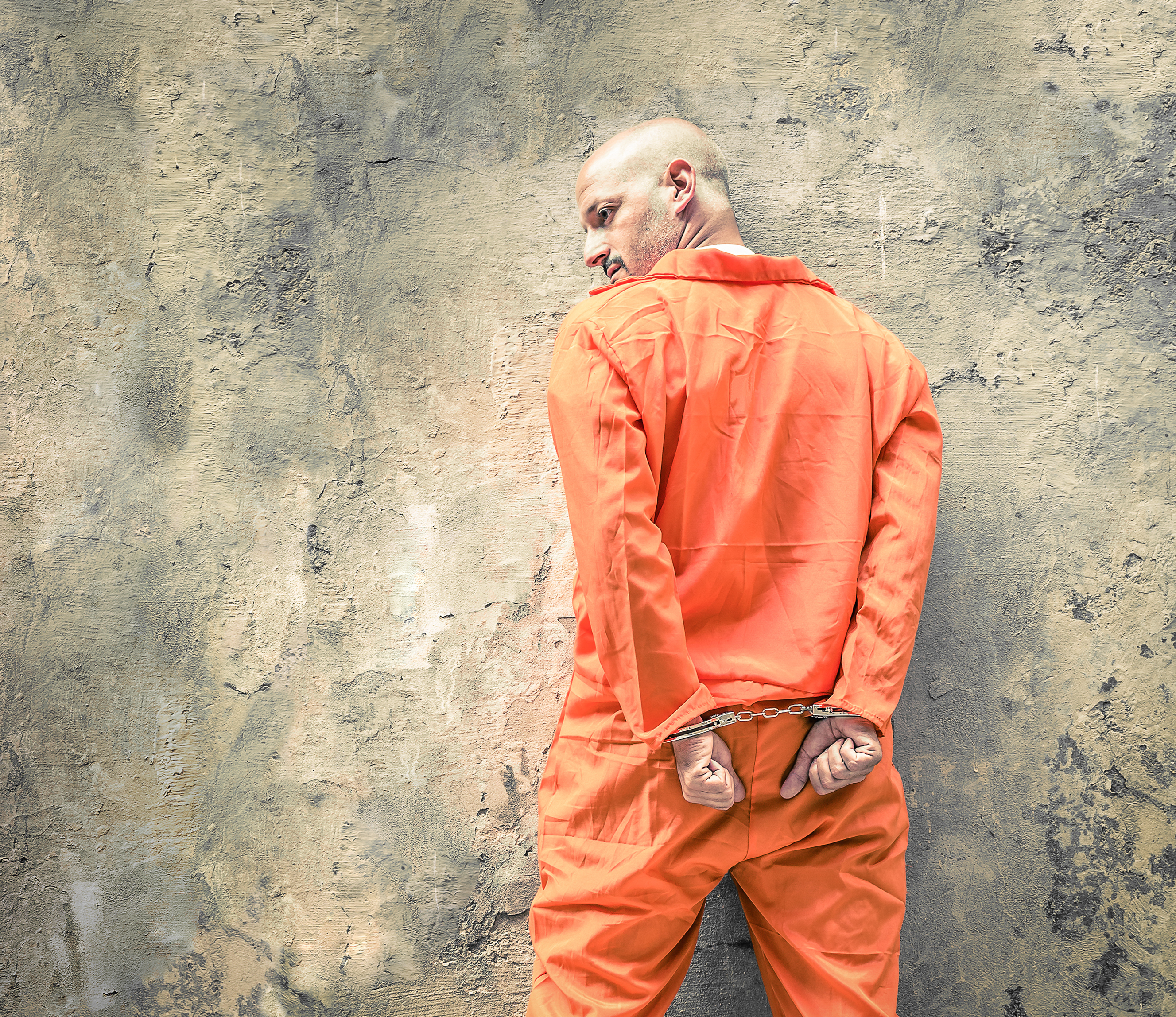 Rear View Of Man With Handcuffs Standing Against Wall