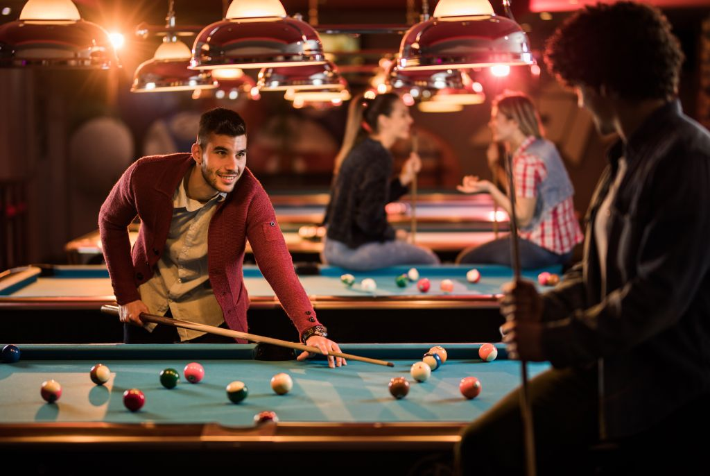 Happy man talking to his friend while playing snooker in a bar.