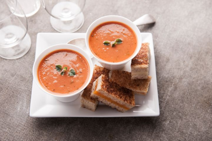 Sliced grilled cheese sandwich and tomato soup