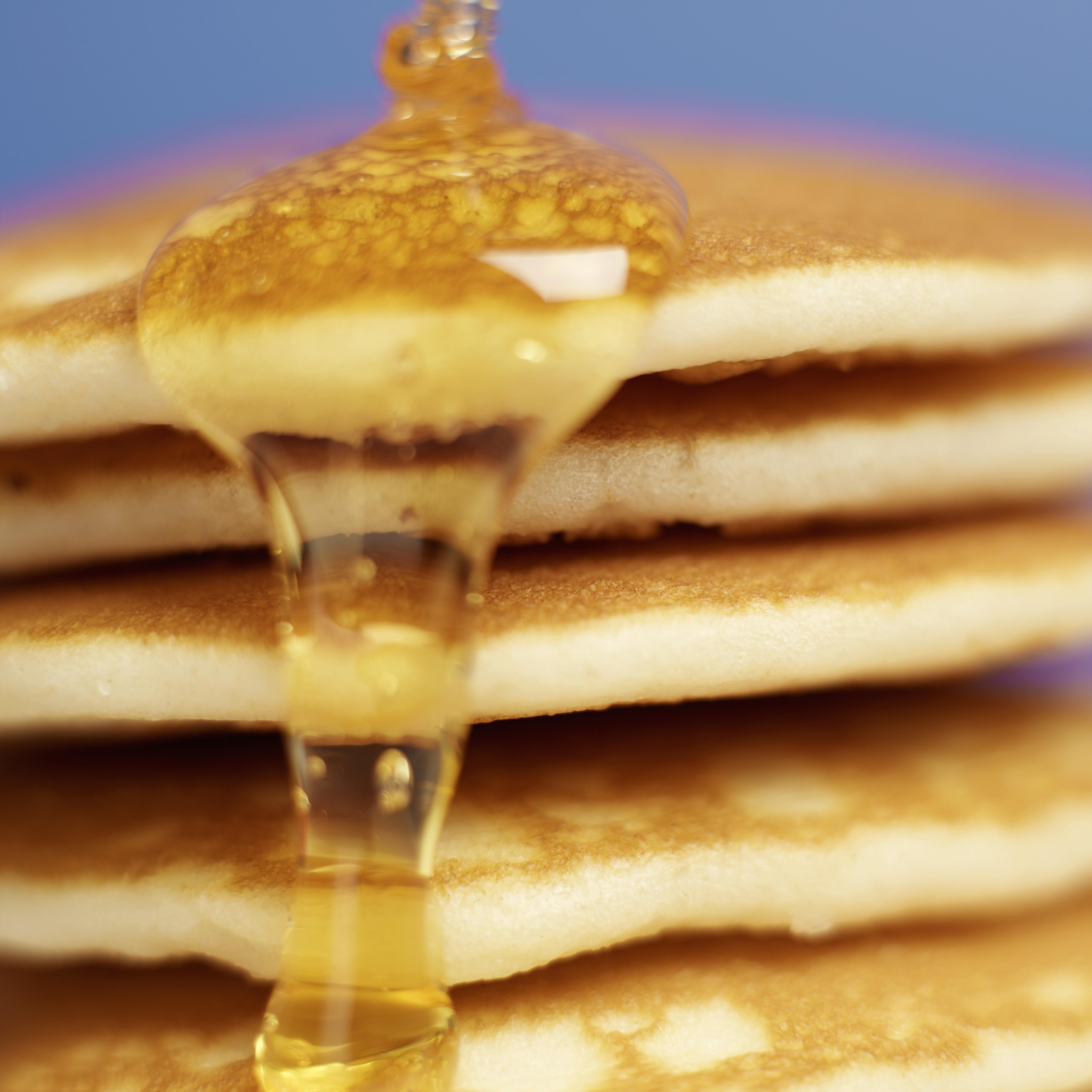 Close-up of pancakes stacked high with syrup being poured over them