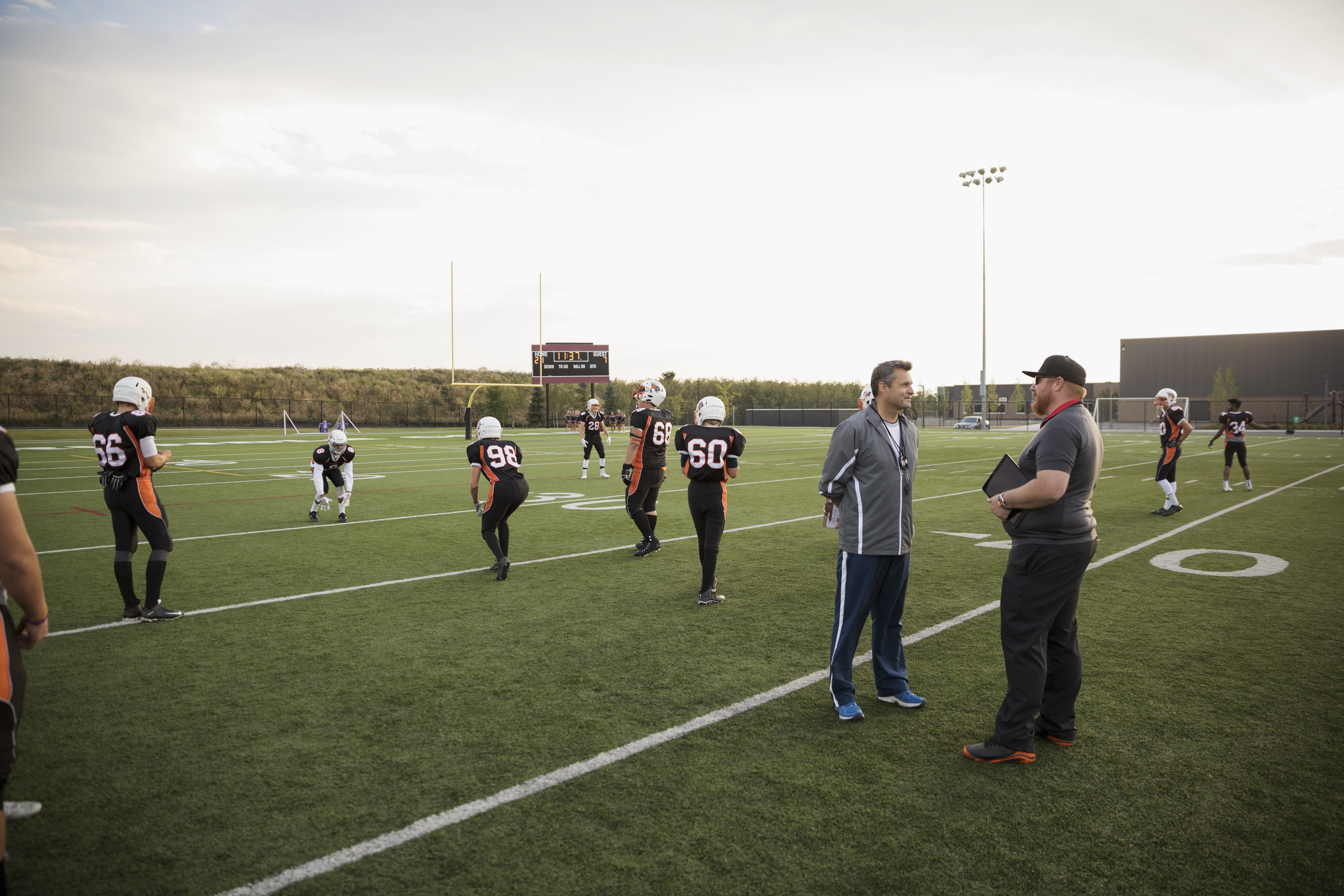 Coaches talking near teenage boy high school football team on football field
