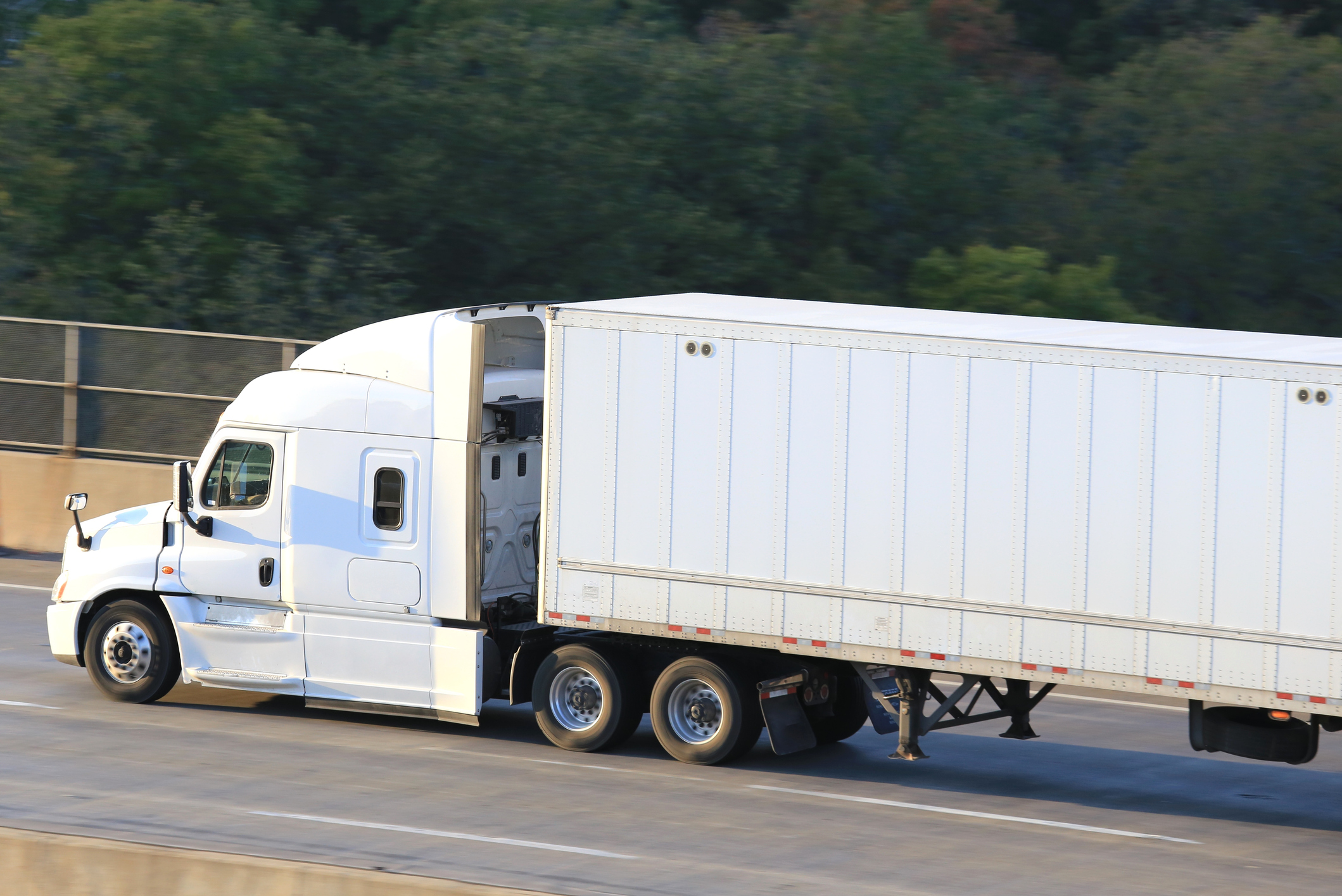 Side view of a moving semi truck on a highway bridge