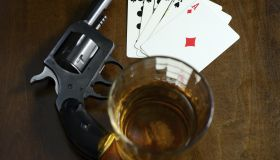 old west poker game with pistol, alcohol and a winning hand
