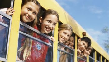 Group of children in a school bus, looking out the window