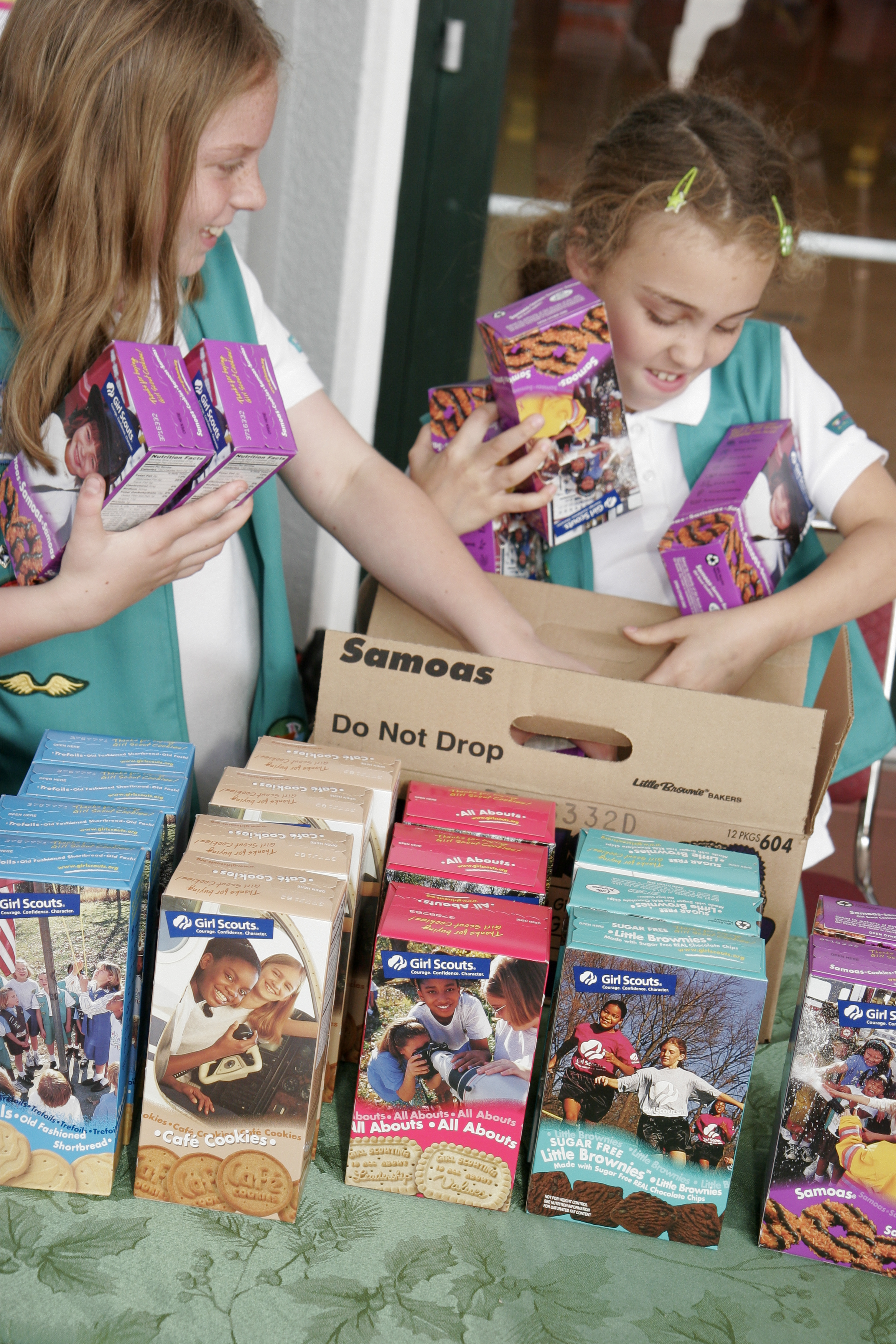 Girl Scouts selling boxes of cookies