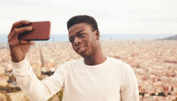 Man taking selfie through smart phone against city