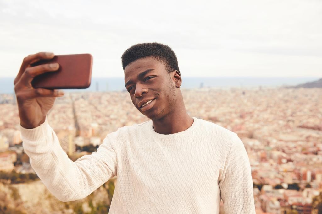 Man taking selfie through smart phone against city