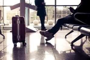 Low Section Of Woman With Luggage Sitting On Chair Against Window At Airport