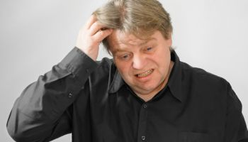 Frustrated Man With Hand In Hair Against Gray Background