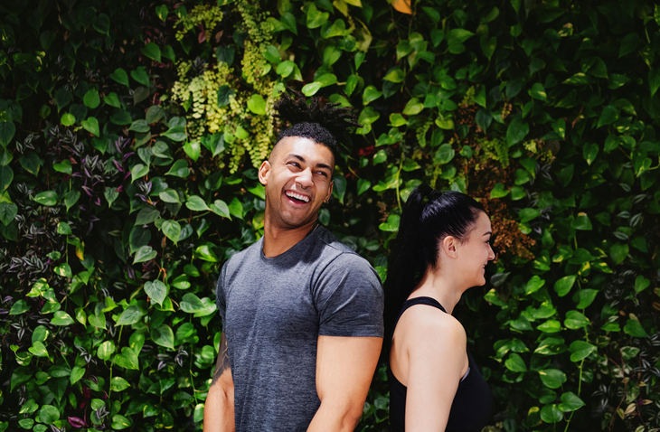 Side view of young couple standing back to back outdoors against green background.