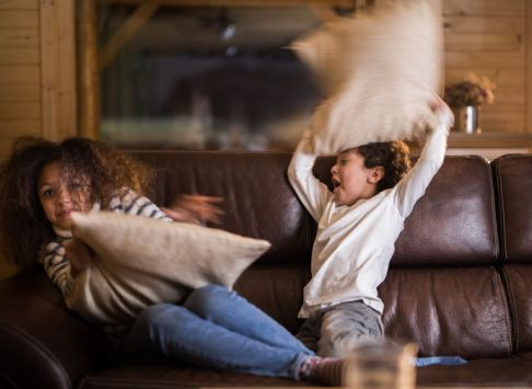 Playful African American girl and boy having a pillow fight at home.