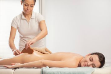 Anti cellulite massage. Mederotherapy. Rolling Pin Massage. Massage Therapist doing healing massage with rolling pin or battledore . Woman enjoying in relaxing massaging at health spa treatment.