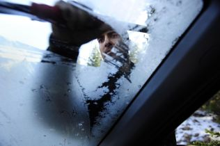 Neel Kashkari scraping frost from the windshield of his SUV