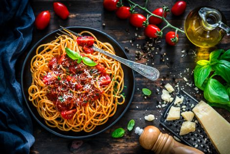 Spaghetti with tomato sauce shot on rustic wooden table