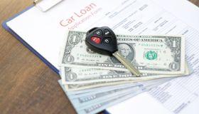 Car loan application with car keys and money