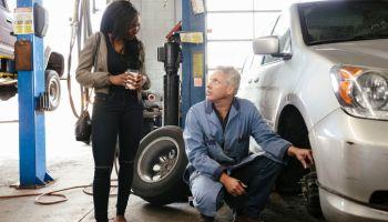 Mechanic changing wheel on female customer's car in garage