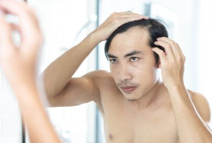 Mid Adult Man Looking In Mirror While Touching His Receding Hairline At Bathroom