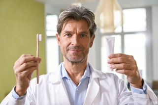 Portrait of dentist holding toothbrush and toothpaste in his medical practice