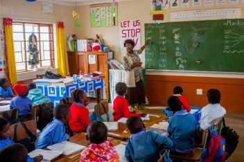 Students and teacher inside a first grade classroom of a...