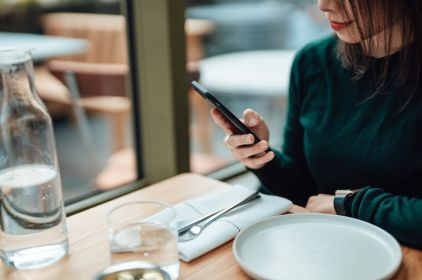 Young Woman Using Smart Phone While Relaxing At A Restaurant